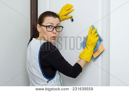 Housewife Woman Looks In The Peephole Of The Front Door In The Apartment, Emotion Of Surprise.