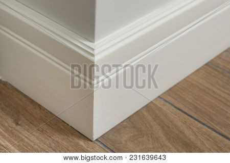 Molding in the interior, baseboard corner. Light matte wall with tiles immitating hardwood flooring. poster