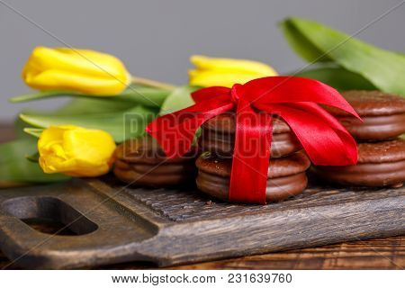 Flowers And Treats On A Beautiful Wooden Board With A Pattern. Yellow Tulips And Chocolate Cookies T
