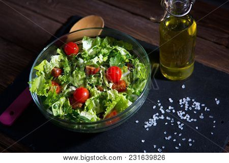 Fresh Mix Salad Leaves With Tomato In Bowl On Black Shale Surface On Wooden Background.