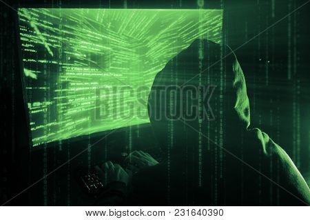 A Man Hacker In A Hood In A Dark Room Works With The Program Code
