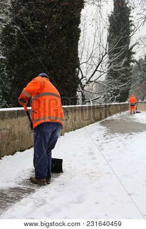 Sweeper On The Sidewalk As He Shovels The Snow After The Snowfall