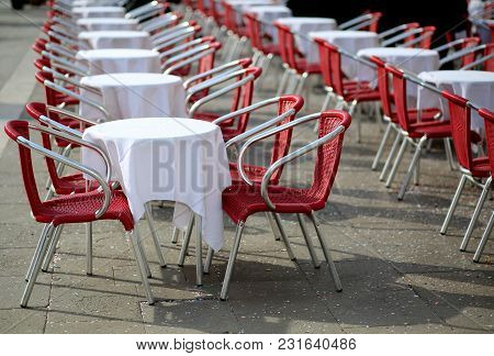 Tables And Red Chairs In An Alfresco Cafe In The Main Square Of An European City