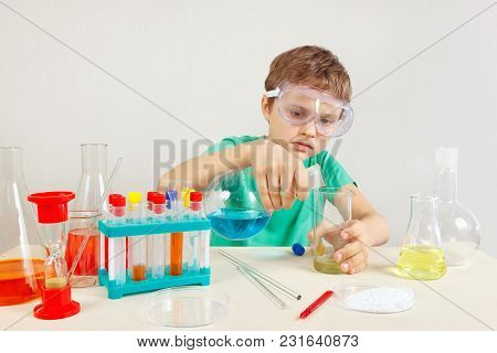 Young Smart Boy In Safety Glasses Doing Chemical Experiments In The Laboratory