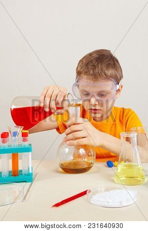 Little Serious Boy In Safety Goggles Studies Chemical Practice In The Laboratory