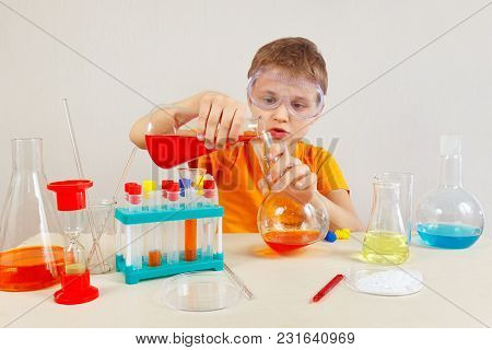 Young Smart Boy In Safety Goggles Studies Chemical Practice In The Laboratory
