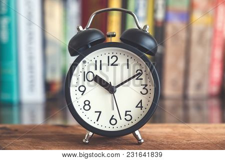 Closeup Image Of A Black Alarm Clock On Wooden Table With Blur Bookshelf In Background