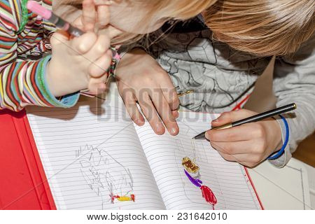 Left Handed Young Boy And Sister Painting In A Book.