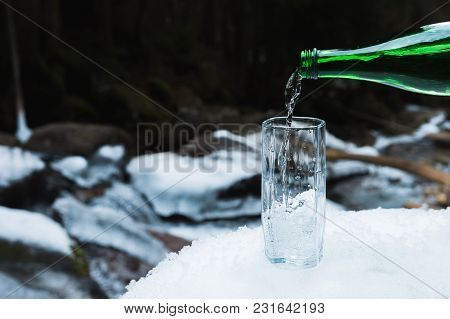 Mineral Mineral Water Is Poured From A Glass Green Bottle Into A Clear Glass Beaker. A Glass Stands