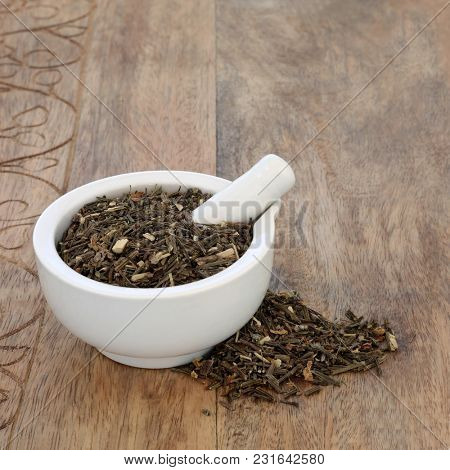 Broom leaf herb used in herbal medicine as a diuretic, can regulate heart rate and is a uterine stimulant and has other health benefits. In a mortar with pestle on rustic wood.  Cytisus scoparius.