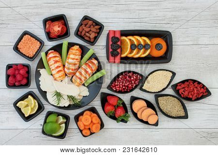 Diet health food dieting concept with high protein seafood and chicken, fruit, vegetables, nuts, legumes, grain and tribulus terrestris herb used as appetite suppressant.  Top view. on rustic wood.