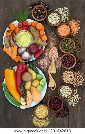 Health food concept with fresh vegetables, pulses, herbs, spice, himalayan salt and olive oil with foods high in vitamins, minerals, smart carbs, anthocyanins, antioxidants and fibre, top view on oak.