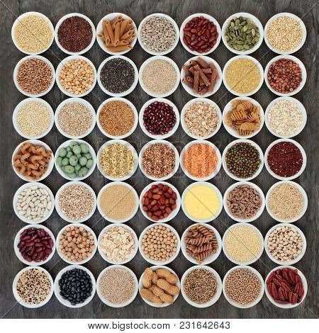 Macrobiotic health food selection of legumes, seeds, nuts, grains, cereals and whole wheat pasta with super foods high in protein, omega 3, anthocyanins, antioxidants, minerals and vitamins. Top view.