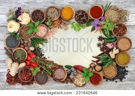 Spice and herb abstract border with fresh and dried herbs and spices on parchment paper and rustic wood background. Top view.