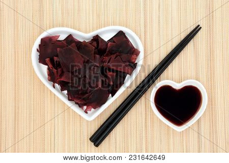 Dulse seaweed health food in a heart shaped dish with low sodium soy sauce and chopsticks on bamboo background. Super food very high in minerals and protein.