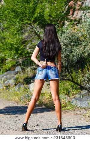 Young Attractive Brunette Girl With Long Legs And Sexy Booty Shows Sign Middle Finger Up. Outdoors A