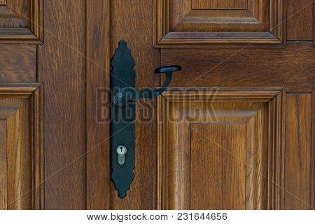 Black Vintage Metal Door Handle On Brown Wooden Doors.
