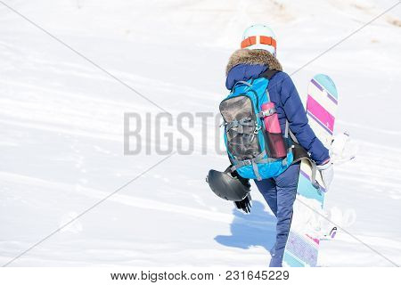 Image From Back Of Woman In Helmet With Backpack And Snowboard In Winter Park In Winter