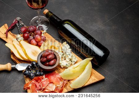 Meat Plate Antipasti Snack With Prosciutto Ham, Blue Cheese, Melon, Grapes, Olives On Wooden Serving