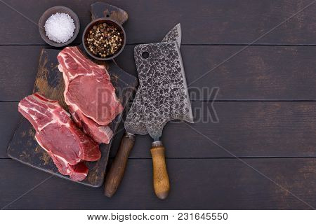 Raw Beef Steak With Bone On Wooden Board And Table With Copy Space