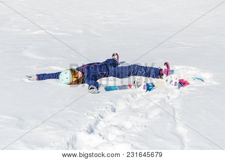Photo Of Sporty Woman Lying In Snow With Snowboard In Winter