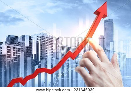 Hand Pointing At Abstract Upward Red Business Chart Arrow On City And Sky Background. Growth And Fin