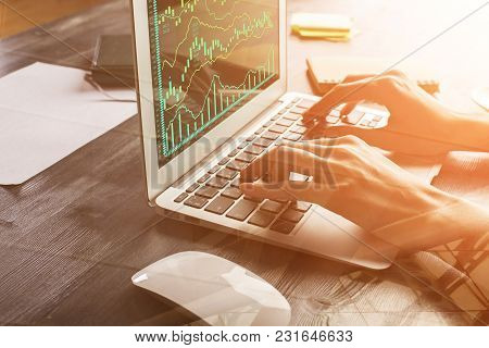 Close Up Of Female Hands Using Laptop With Forex Chart At Modern Office Desk With Items. Filtered Im