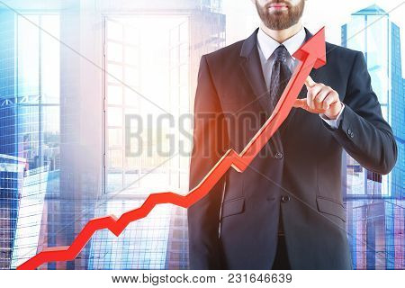 Businessman Pointing At Abstract Upward Red Business Chart Arrow On City And Background. Startup And