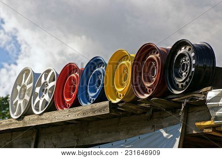 Row Of Old Colored Discs Against The Sky And Clouds