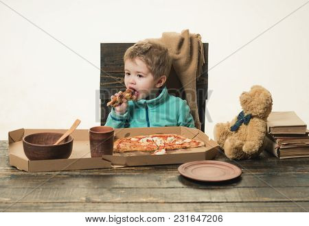 Child Eats Pizza At Wooden Table Isolated On White Background. Homemade Rustic Food In Italy. Lunch
