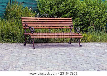 Empty Wooden Bench Of Brown Color On The Sidewalk Near The Lawn