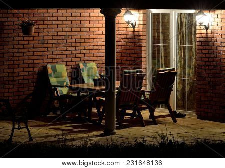Modern House Garden Terrace Patio Lined With Bricks With Garden Furniture And Antique Column At Nigh