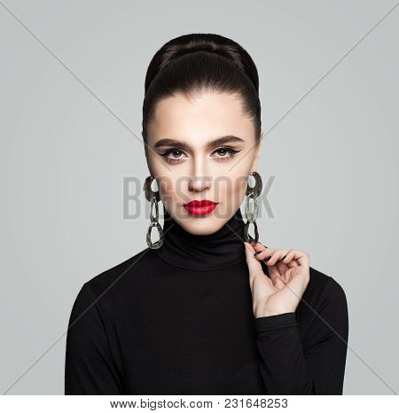 Elegant Young Woman With Hair Bun Hairstyle, Red Lips And Eyeliner Makeup. Cute Female Model In Blac
