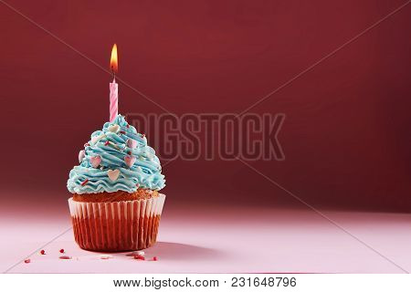 Muffin Or A Small Cake With A Burning Candle. Concept Of Congratulation, Holiday.
