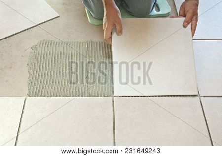 Man Placing Ceramic Floor Tile In Position Over Adhesive.