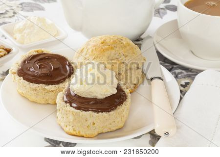 Homemade Walnut Scone With Chocolate Spread And Cream, Served With A Cup Of Tea.