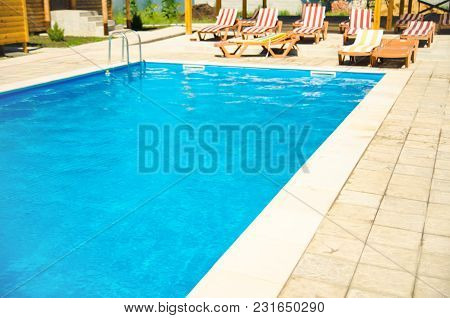 A Pool With Chaise Longues In Hotel