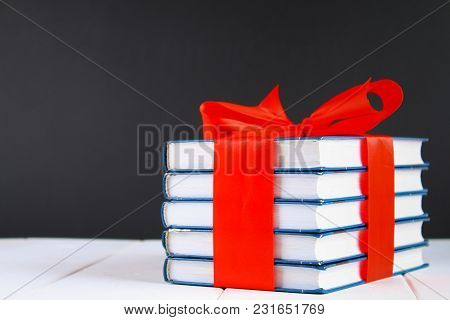 A Pile Of Books Tied With A Red Ribbon On A White Wooden Table. A Gift On The Background Of A Chalkb