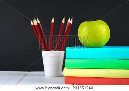 A Pile Of Books And Stationery On A Chalkboard Background. Work Desk, Education, School