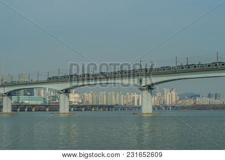 Subway train on bride crossing river with city highrise buildings in the background under clear blue sky poster