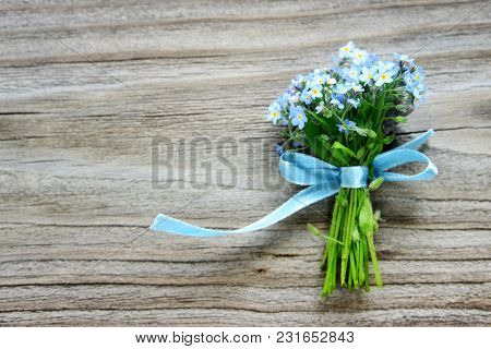 Small Bouquet Of Blue Forget-me-not Flowers, Tied With A Blue Ribbon, On The Background Of Old Woode