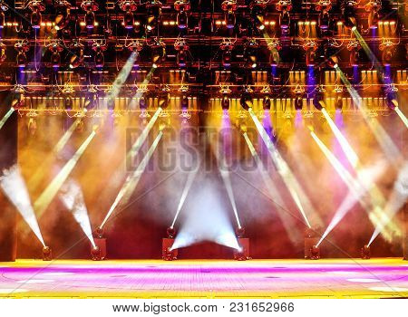 Illuminated Empty Concert Stage With Haze And Rays Of Pink And Yellow Light. Background For Music Sh