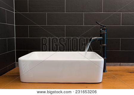Modern White Square Sink In Bathroom With Black Tiles And Black Faucet In Shape Of Bamboo. Modern Ba