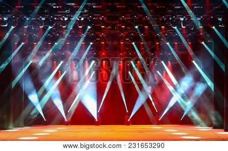 Illuminated Empty Concert Stage With Haze And Rays Of Blue And Red Light. Background For Music Show