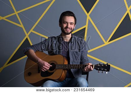 Young Handsome Man With A Beard Holding A Guitar