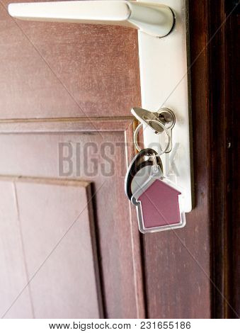 House Key On House Shaped Keyring In Lock Of Entrance Brown Door