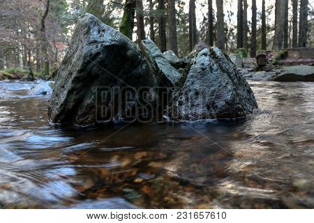 Large Rocks In The Middle Of A Woodland Stream