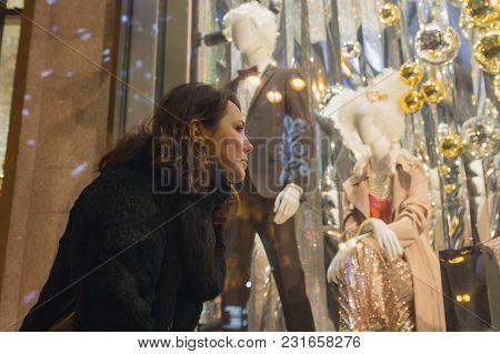 Woman Looks In A Show-window Of Shop. People