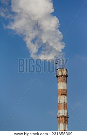 Smoking Pipe Of The Boiler Room Against The Sky. Ecology