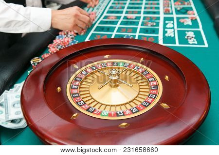 Roulette For Playing Poker On The Table Background With Players